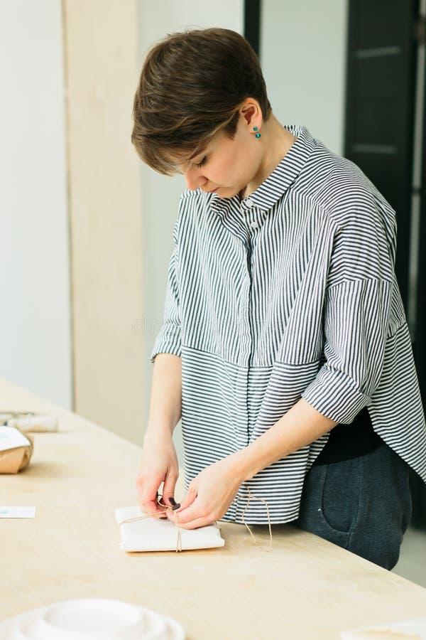 La muchacha embala un regalo en una tabla de madera imagen de archivo
