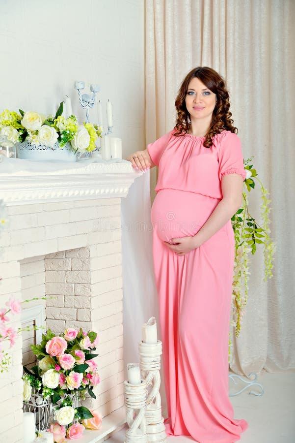 La muchacha embarazada hermosa en un vestido rosado que presenta en estudio en un fondo colorea, apoya el abdomen y sonríe foto de archivo libre de regalías