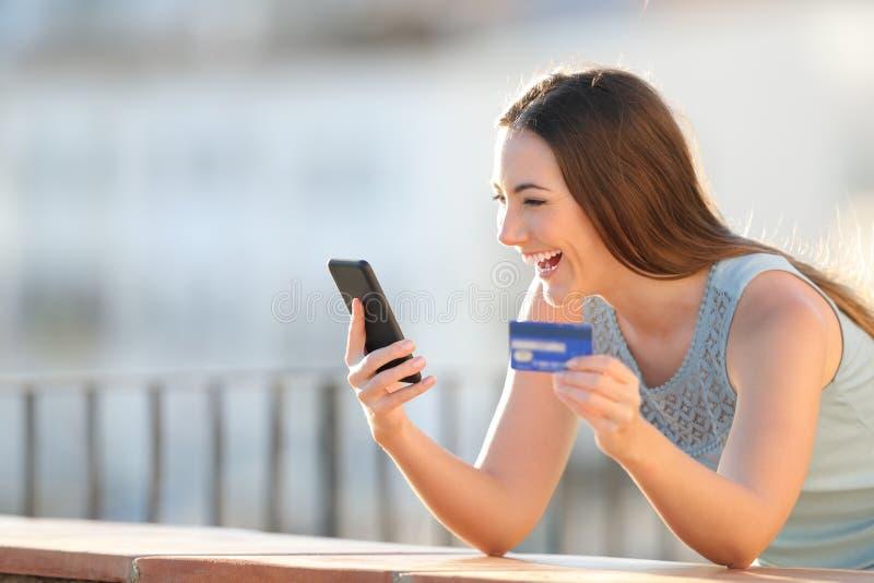 La muchacha emocionada está pagando con la tarjeta y el teléfono de crédito foto de archivo libre de regalías
