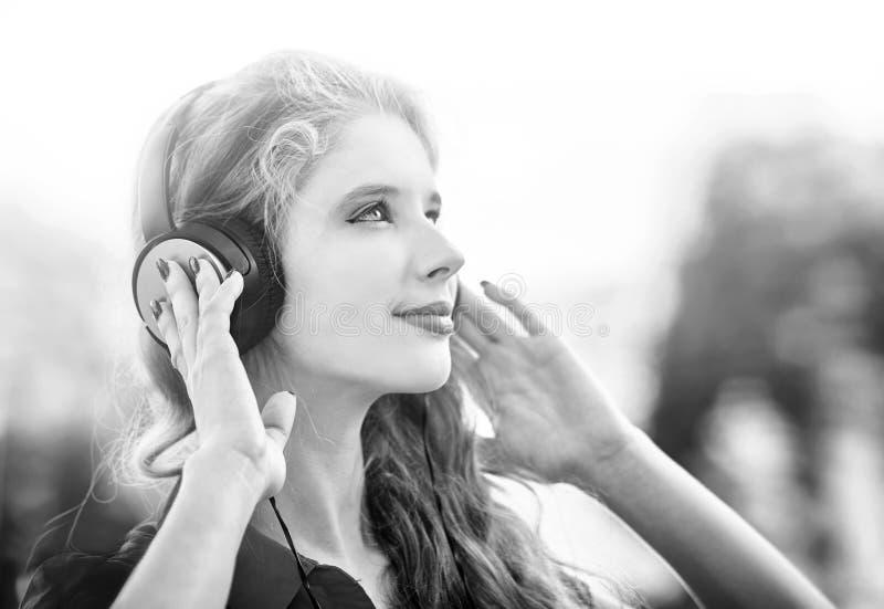 La muchacha en auriculares escucha la m?sica en ciudad Rebecca 36 fotografía de archivo libre de regalías