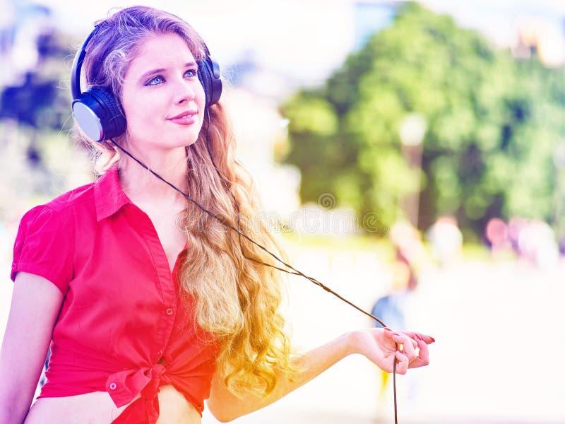 La muchacha en auriculares y camisa roja escucha la música mp3 fotografía de archivo libre de regalías