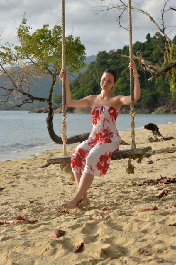 La muchacha en blanco con las flores rojas se viste en la playa fotografía de archivo libre de regalías