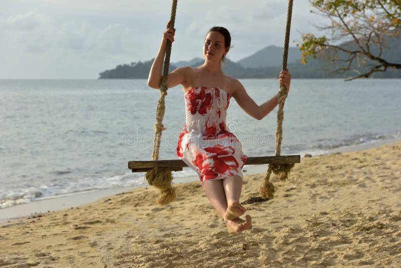 La muchacha en blanco con las flores rojas se viste en la playa imagen de archivo libre de regalías