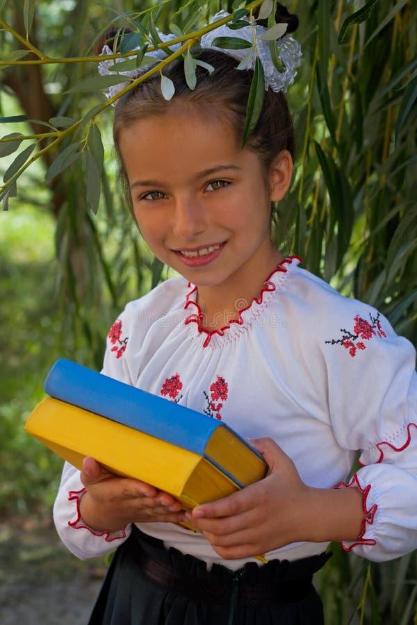 La muchacha en bordado reserva con la bandera del ucraniano del color imagen de archivo libre de regalías
