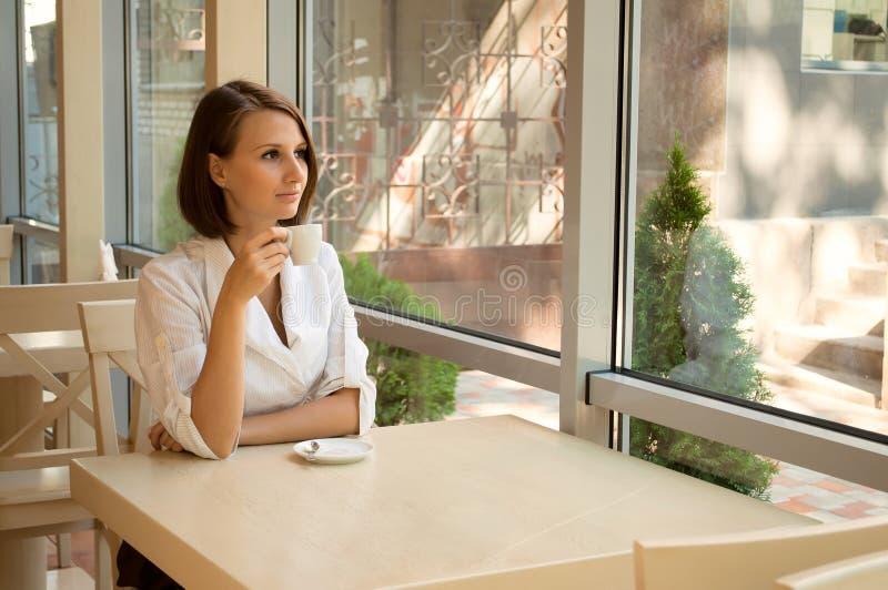 La muchacha en café detrás de una taza de café imágenes de archivo libres de regalías