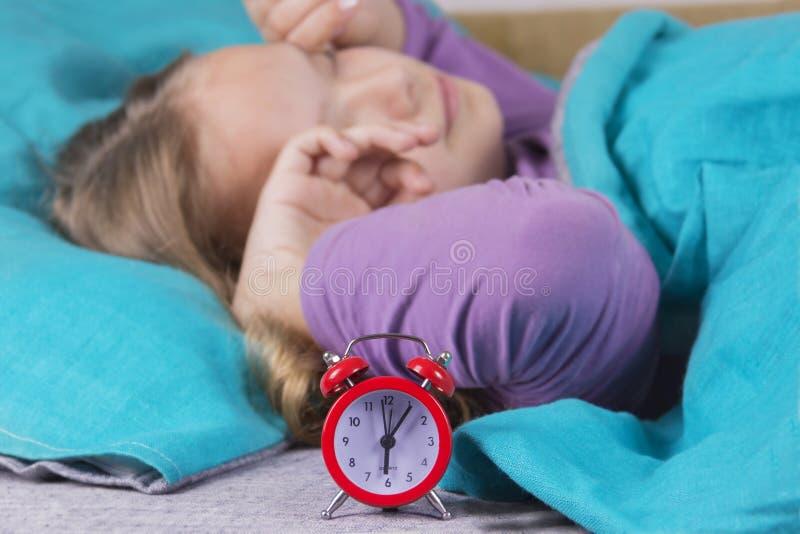 La muchacha en la cama despierta del sonido del despertador y estira antes de subir a partir de la mañana fotografía de archivo libre de regalías