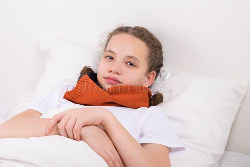 La muchacha en la cama se calienta el cuello con una bufanda, una garganta dolorida fotografía de archivo libre de regalías