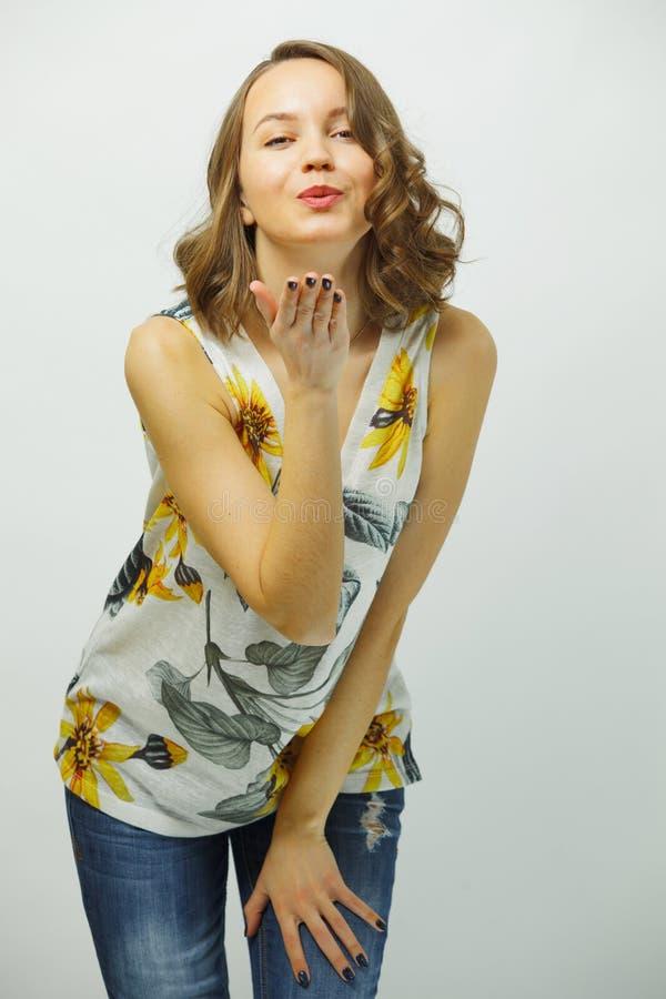 La muchacha en la camisa del verano le envía beso del aire sobre blanco aislada foto de archivo