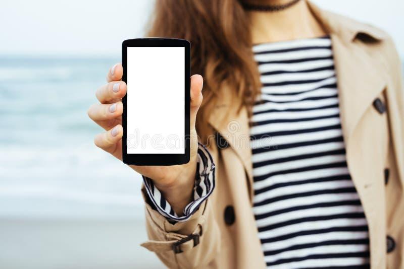 La muchacha en capa beige y camiseta rayada muestra un phon de la pantalla en blanco fotografía de archivo