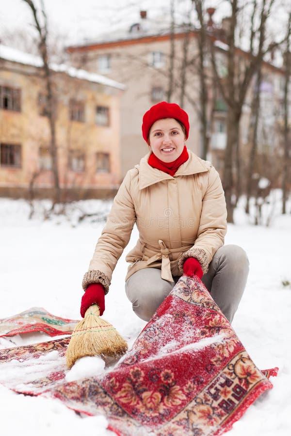 La muchacha en casquillo rojo limpia la alfombra con nieve imagen de archivo