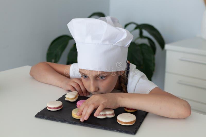 La muchacha en la cocina con los macarrones de la placa fotografía de archivo
