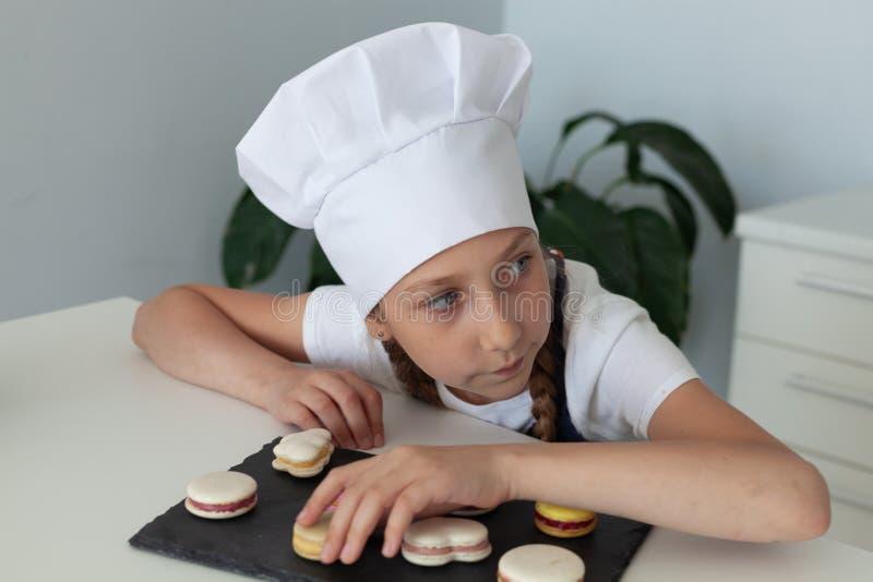 La muchacha en la cocina con los macarrones de la placa fotos de archivo