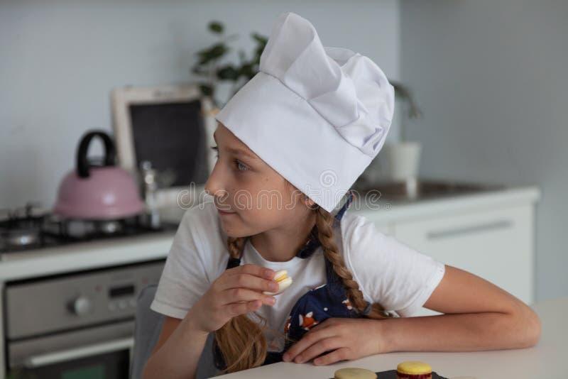 La muchacha en la cocina con los macarrones de la placa foto de archivo