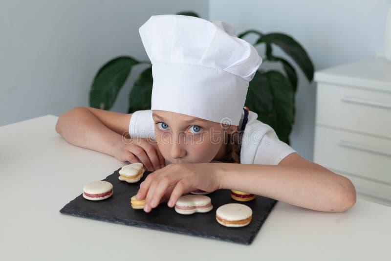 La muchacha en la cocina con los macarrones de la placa imagenes de archivo