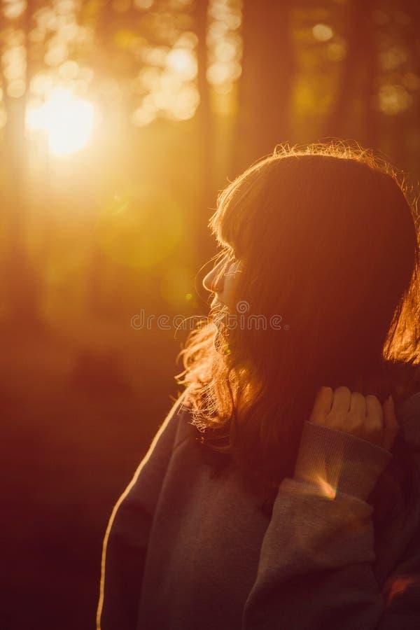 La muchacha en el bosque está mirando la puesta del sol Sun anaranjado fotos de archivo