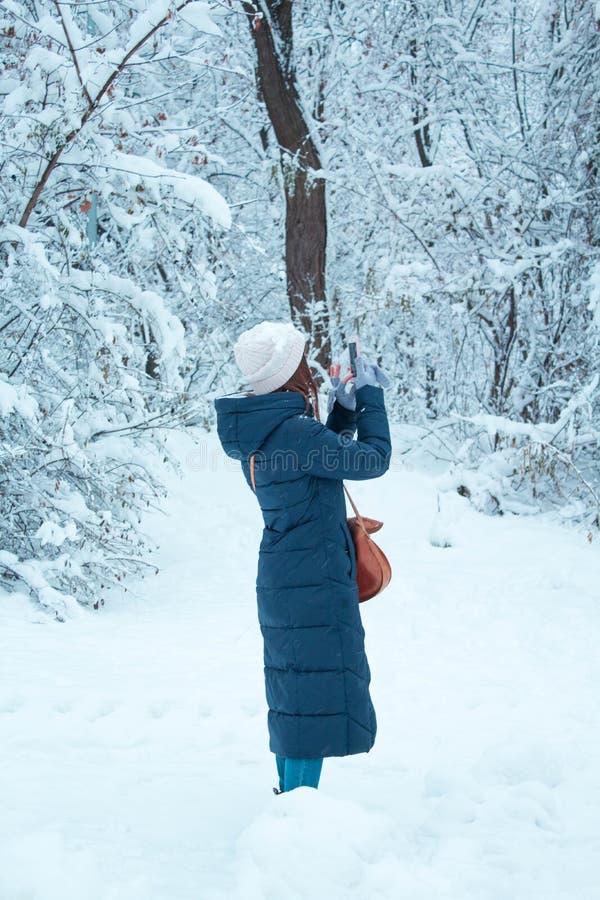 la muchacha en el bosque toma imágenes en su teléfono móvil fotos de archivo