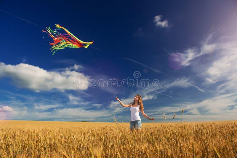 La muchacha en el campo lanza una cometa imagen de archivo