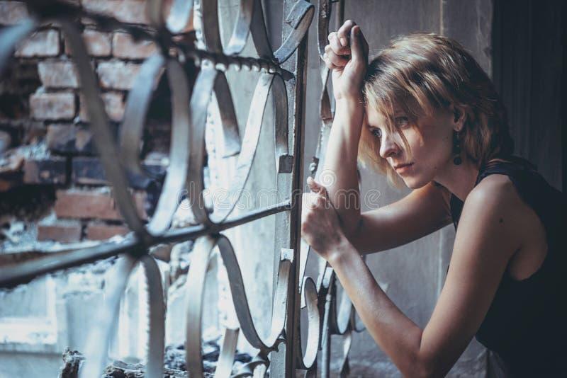 La muchacha en el enrejado Windows fotos de archivo