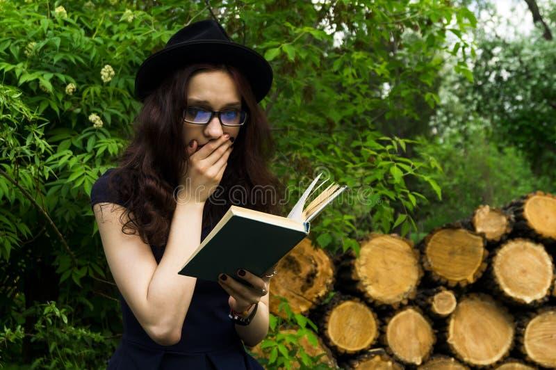 La muchacha en el parque que lee un libro fotos de archivo libres de regalías