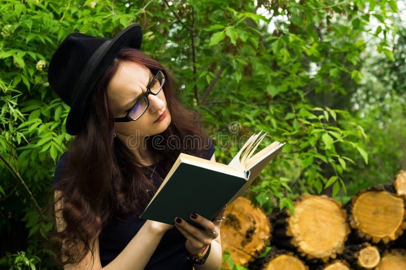 La muchacha en el parque que lee un libro fotos de archivo