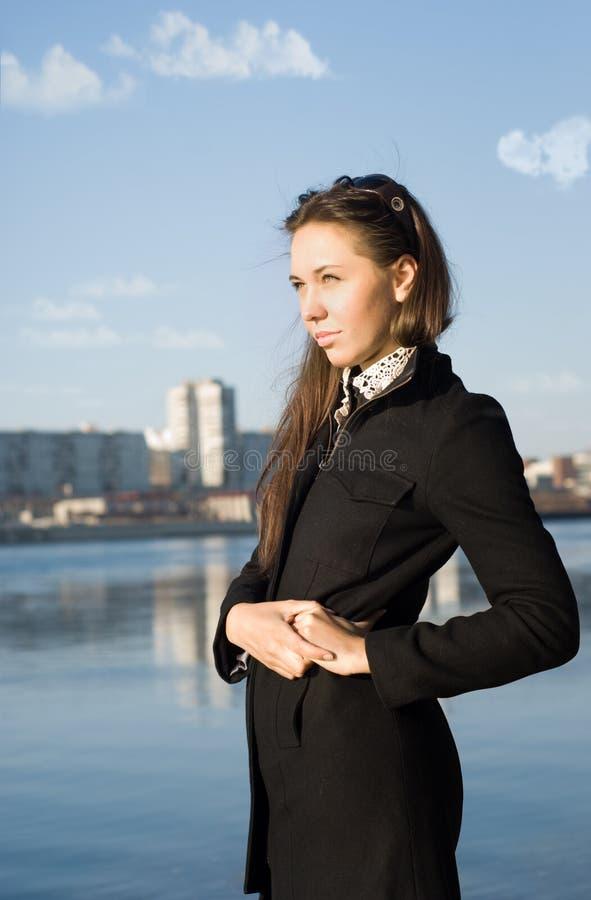 La muchacha en el riverbank fotos de archivo