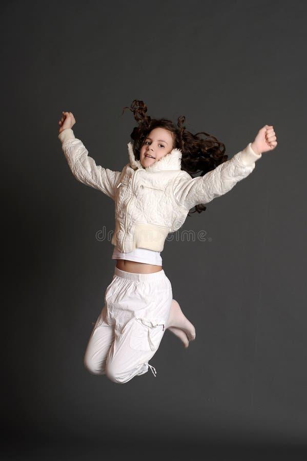 La muchacha en el salto blanco del vestido fotos de archivo