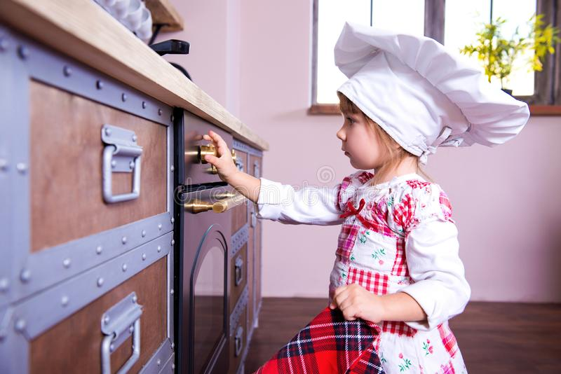 La muchacha en el sombrero del cocinero está poniendo las galletas del pan de jengibre en el horno fotos de archivo libres de regalías