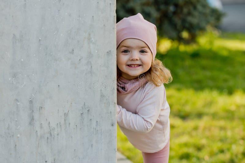 La muchacha en el sombrero rosado, ropa sonr?e en la pared gris foto de archivo