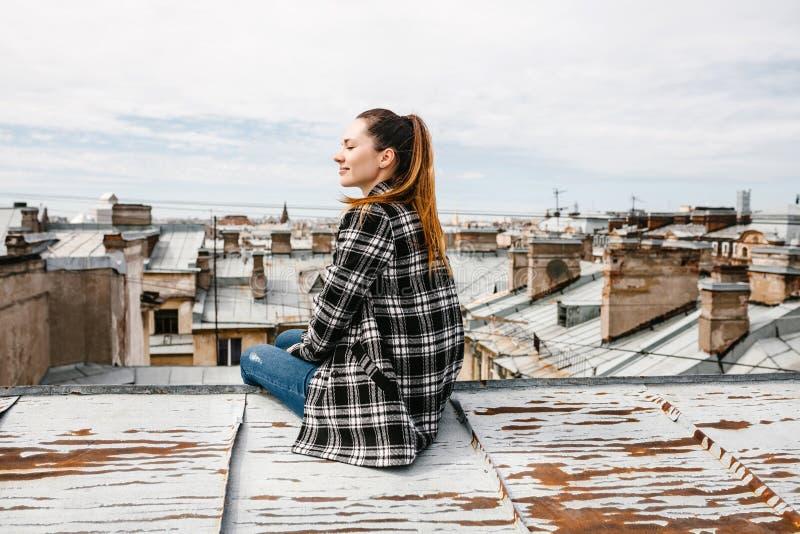 La muchacha en el tejado de la casa fotos de archivo