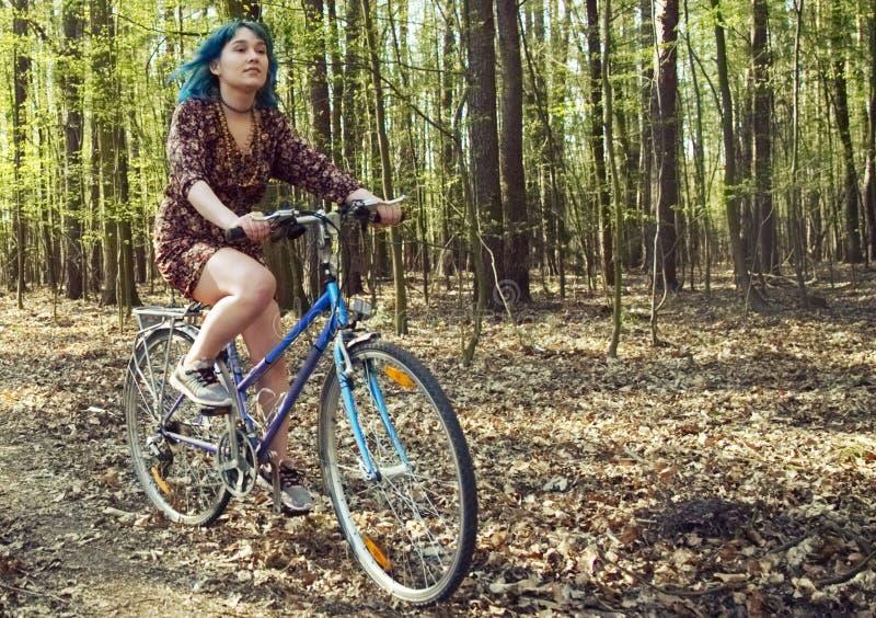 La muchacha en el vestido monta una bicicleta a trav?s del bosque fotografía de archivo