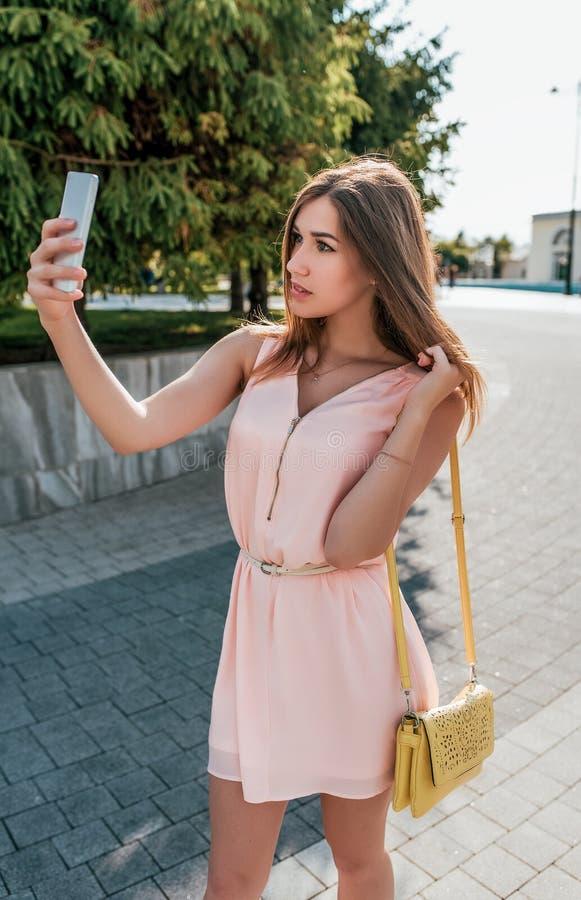 La muchacha en el vestido, verano en ciudad, se coloca en su teléfono de la mano, llamada video, fotografía de sí misma, uso del  imagen de archivo
