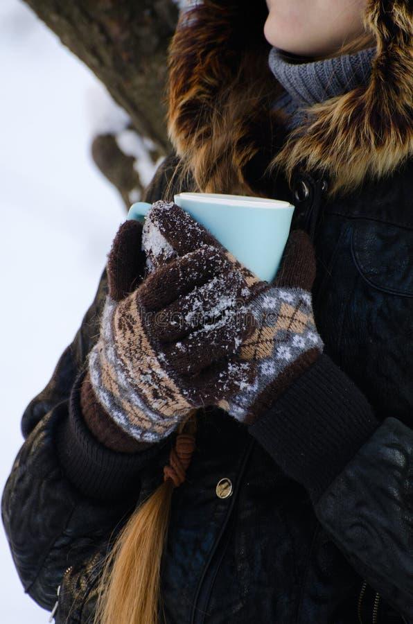 La muchacha en guantes abrazó su taza de té, fondo nevoso blanco, cara no es visible fotos de archivo