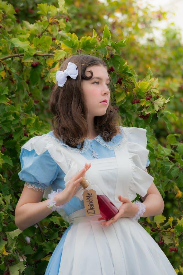 La muchacha en imagen de la bebida de las bebidas de la heroína del cuento de hadas de la botella de cristal con una etiqueta me  imagen de archivo libre de regalías