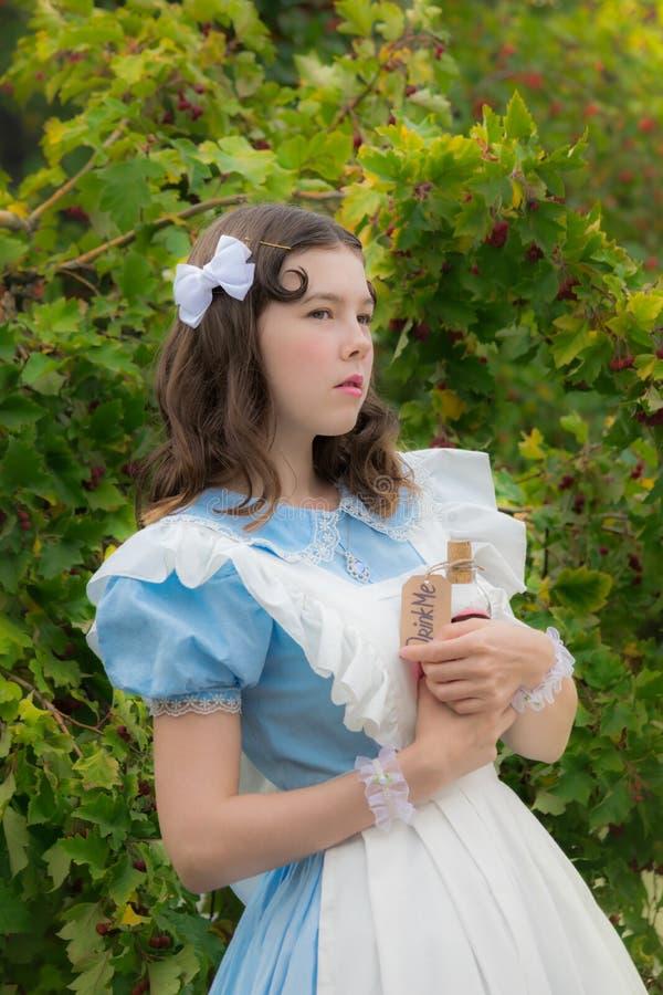 La muchacha en imagen de la heroína del cuento de hadas duda y sosteniendo una botella de cristal con una etiqueta bébame fotografía de archivo libre de regalías