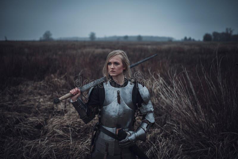 La muchacha en la imagen del arco del ` de Jeanne d en armadura y con la espada en sus manos se coloca en prado primer fotografía de archivo libre de regalías