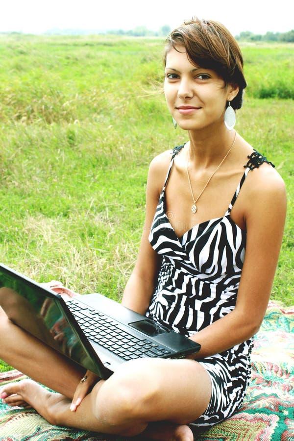 La muchacha en la naturaleza de una caja del ordenador portátil foto de archivo
