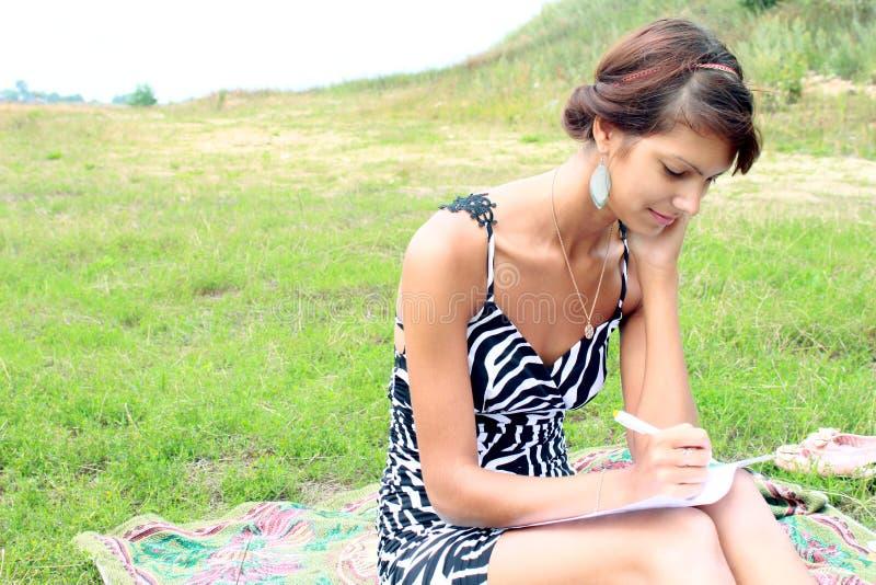 La muchacha en la naturaleza de una caja del ordenador portátil imagen de archivo libre de regalías