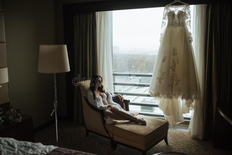 La muchacha en las bragas y las medias blancas se está inclinando en la silla fotografía de archivo libre de regalías