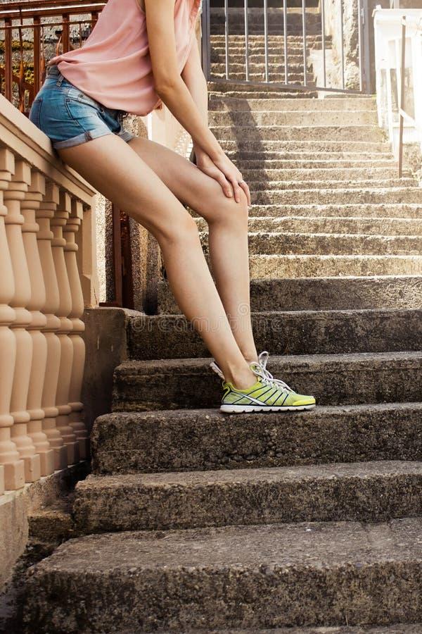 La muchacha en las escaleras en calzados atléticos en el tono del vintage imagen de archivo
