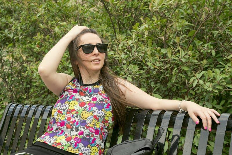 La muchacha en las gafas de sol que llevan del banco imagenes de archivo