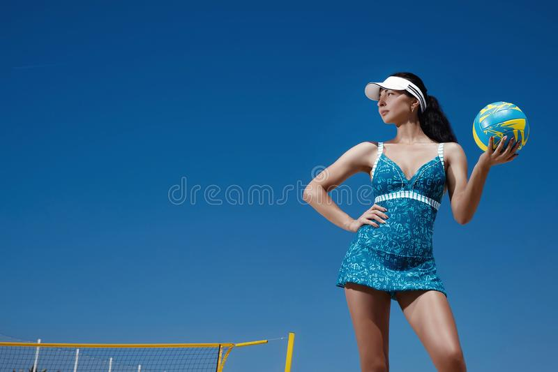La muchacha en los deportes azules se viste con una bola del voleibol foto de archivo