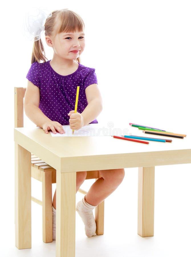 La muchacha en los dibujos de la tabla con los marcadores imagen de archivo libre de regalías