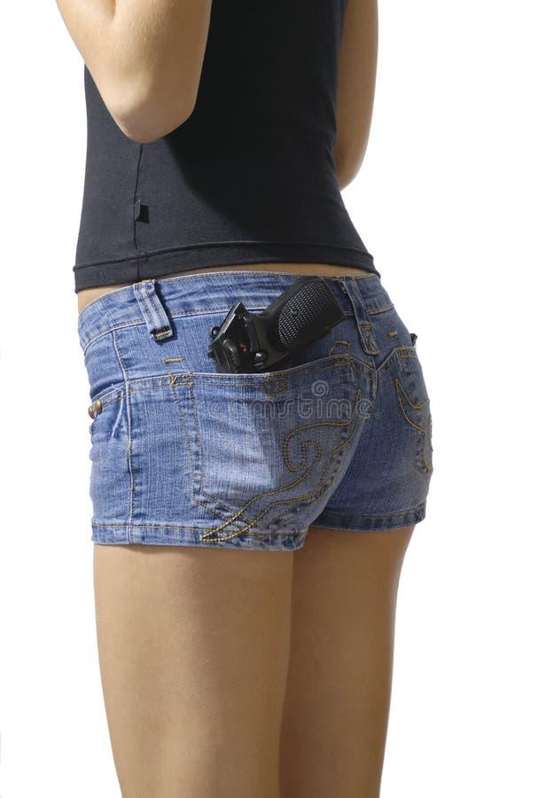 La muchacha en los tejanos pone en cortocircuito cortocircuitos aislados con la pistola en PC posterior imagen de archivo