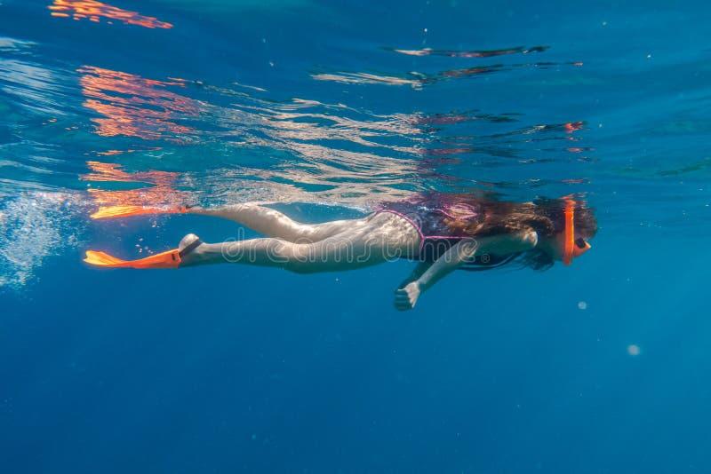 La muchacha en máscara anaranjada de la natación y las aletas se zambullen en el mar profundo imagenes de archivo