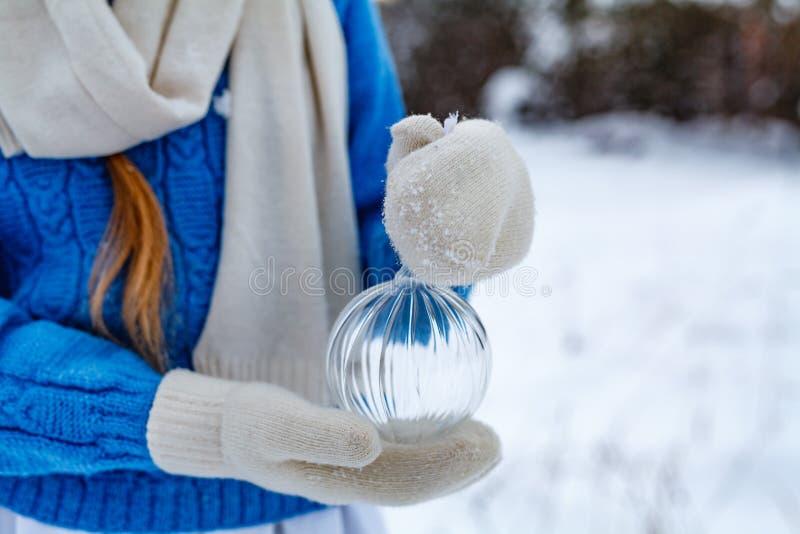 La muchacha en manoplas está sosteniendo una decoración del árbol de navidad fotografía de archivo libre de regalías