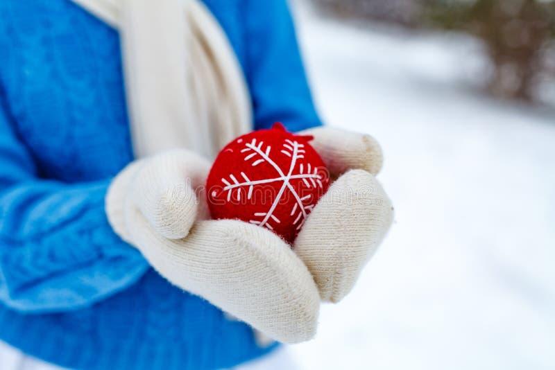 La muchacha en manoplas está sosteniendo una decoración del árbol de navidad imagen de archivo libre de regalías