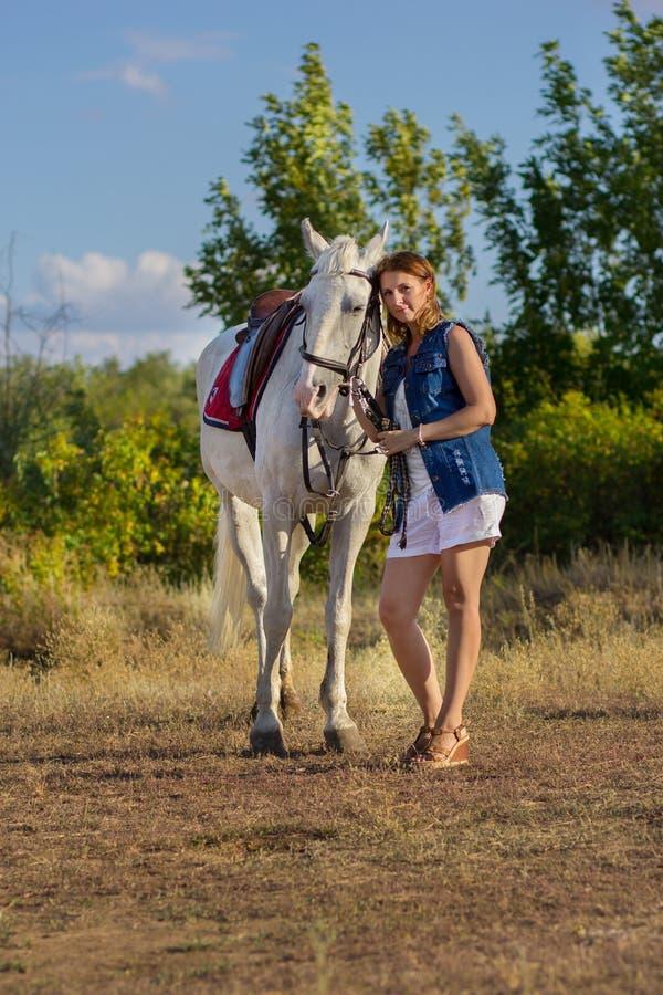 La muchacha en pantalones cortos abraza un caballo blanco imágenes de archivo libres de regalías