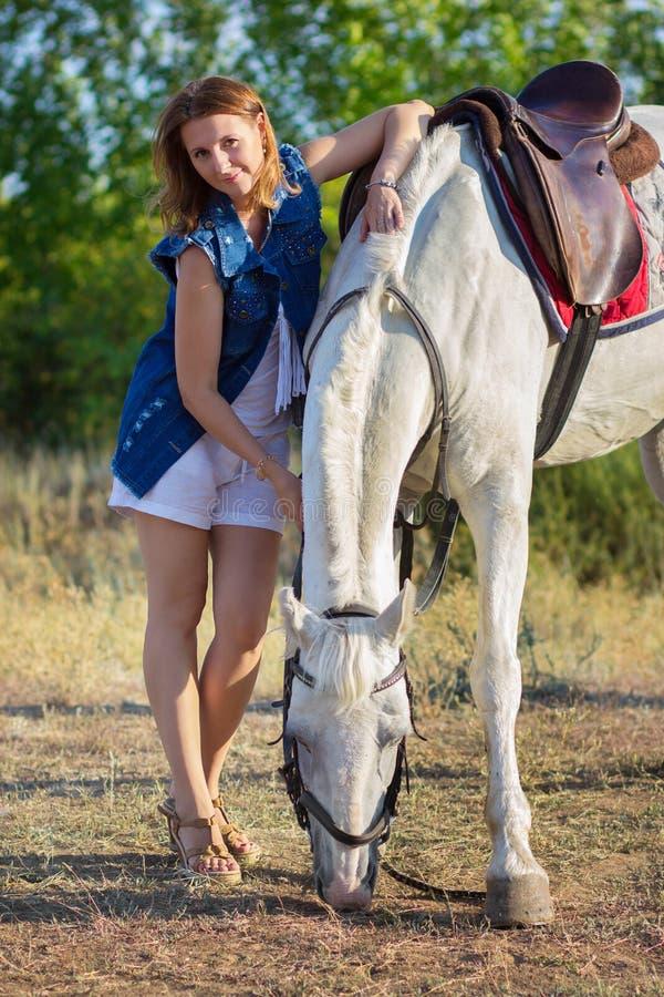 La muchacha en pantalones cortos abraza un caballo blanco imagen de archivo libre de regalías