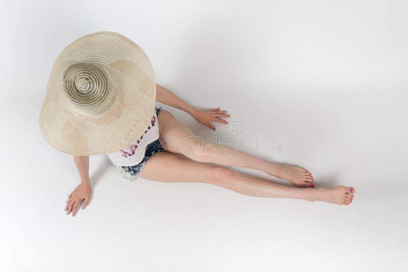 La muchacha en pantalones cortos y sombrero que cubre su cara que se sienta en el fondo blanco aislado foto de archivo libre de regalías