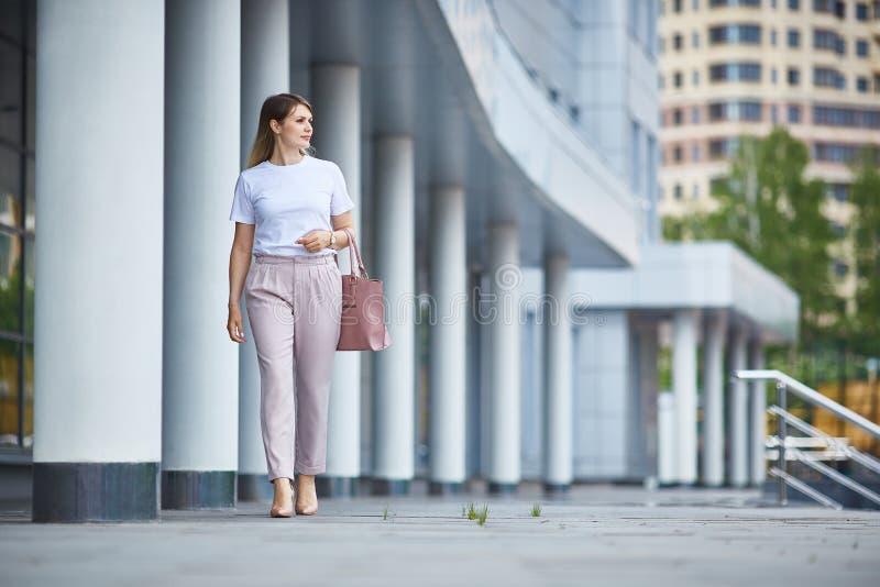 La muchacha en pantalones va cerca del edificio del negocio imagenes de archivo